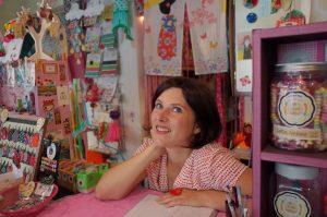 אישה בתספרת קרה ועניי תכלת יושבת ליד שולחן מוקפת ביצירות צבעוניות
