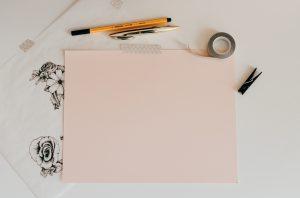 דף ורוד מוצמד למשטח בוואשי טייפ וסביבו שני עטים וואשי טייפ ואטב כביסה וסביבו