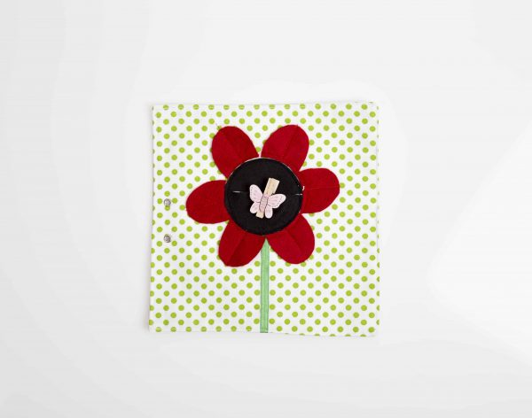 פרח גדול עם מרכז שחור ועלי כותרת אדומים ועליו אטב בצורת פרפר ורוד.