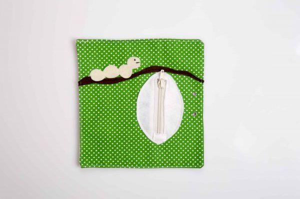 ענף לבד חום על רקע ירוק על הענף זחל לבן וגולם עם רוכסן סגור.