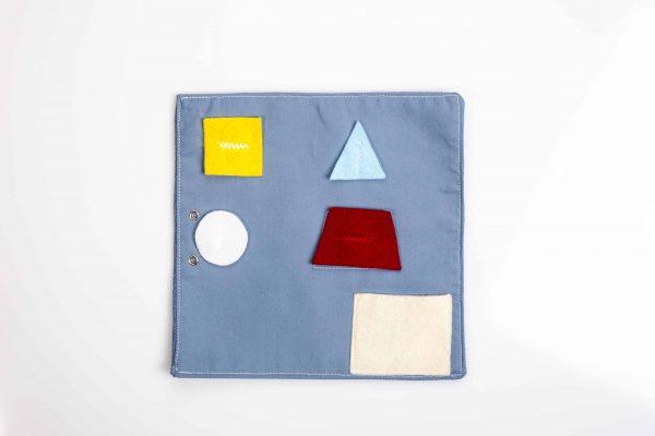 ארבע צורות גאומטריות (ריבוע, משולש, טרפז ועיגול) וכיס שניתן להכניס אותם אליו.