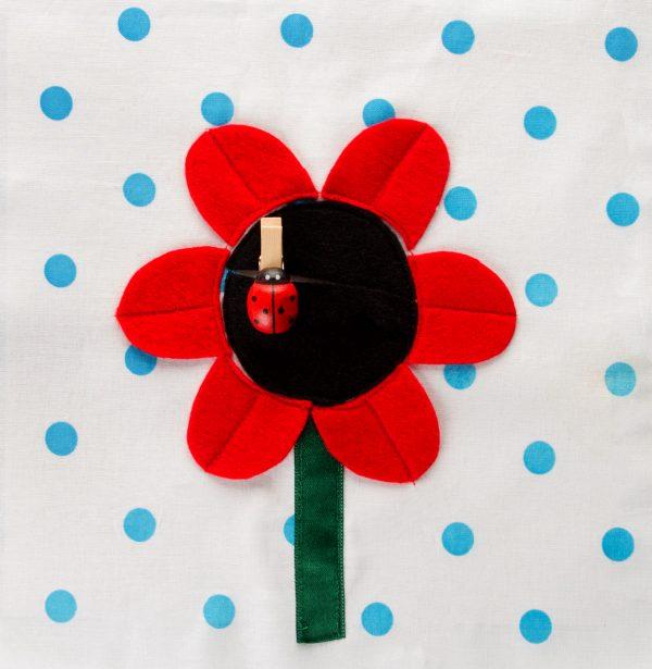 רח גדול עם מרכז שחור ועלי כותרת אדומים ועליו אטב בצורת חיפושית.