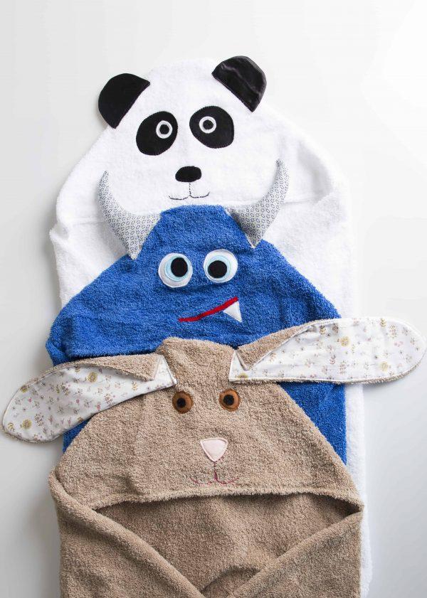 שלוש מגבות מקופלות אחת לבנה בצורת פנדה אחת כחולה בצורת מפלצת ואחת חומב בצורת ארנבת.