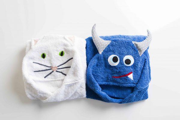 שתי מגבות מקופלות אחת לבנה בצורת חתול ואחת כחולה בצורת מפלצת.