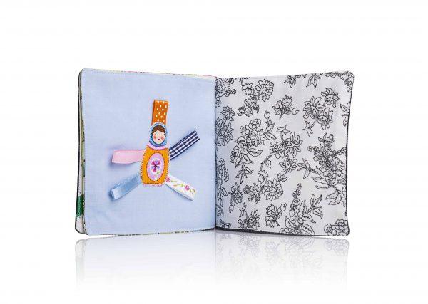 כפולה בספר תינוקות-בד שחור לבן ןבצד השני עיגול עם צורת בבושקה עליו וסביבו שישה סרטים בצבעים שונים.
