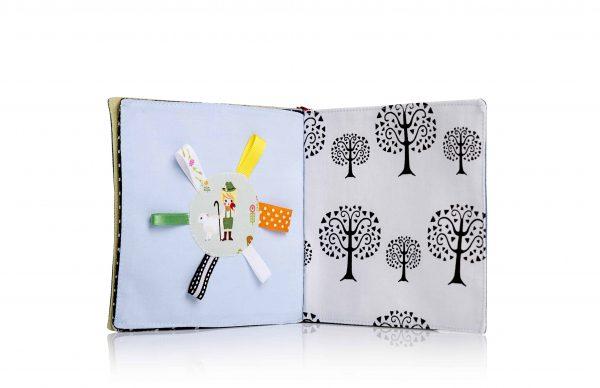 כפולה בספר תינוקות-בד שחור לבן ןבצד השני עיגול עם ילד עליו וסביבו שישה סרטים בצבעים שונים.