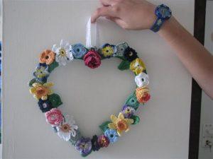 יד מחזיקה מתלה לקיר בצורת לב ועליו פרחים ועלים סרוגים