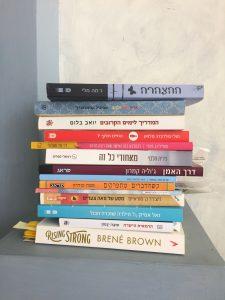 ערימה של ספרים מונחת על מדף צבוע כחול. הספרים בערימה הם: ההצהרה, ארץ עיר ילדה,המדריך לימים הקרובים, החיים חלקי 7, להתלבש כמו האישה שאת רוצה לניות,מאחורי כל זה, דרך האמן,שניים הפוך בבקשה, כשהדברים מתפרקים,על ציר האפשר,מסע של 100 צעדים, הילדה שזכרה הכל,הרמאית הישרה, Rising strong.