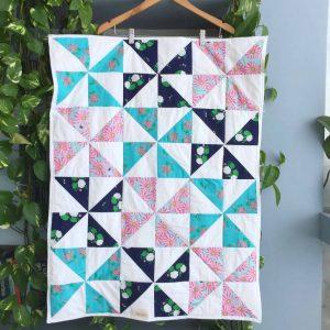 שמיכה בדגם שבשבות בשלושה צבעים כחות כהה, טורקיז ופרחי מרגנית ורודים.