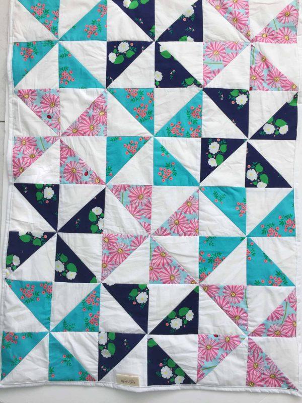 שמיכה בדגם שבשבות בשלושה צבעים כחות כהה, טורקיז ופרחי מרגנית ורודים.צילום מקרוב.