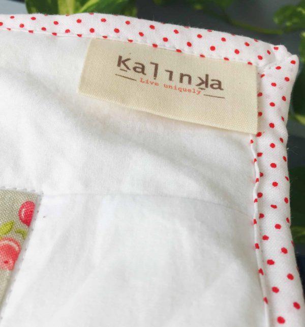 פינת שמיכה הכוללת אמרה בצעי נקודות אדומות על רקע לבן עם תויצ העסק קלחנקה בפינה.