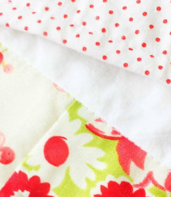 תקריב צד אחורי של שמיכה (נקודות אדומות קטנות על רקע לבן) ליד טלאי בדוגמה פרחונית בצבעי אדום ירוק.