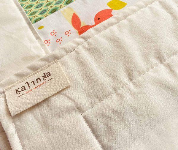 תוית בד תפורה לקצה של שמיכה מקופלת.