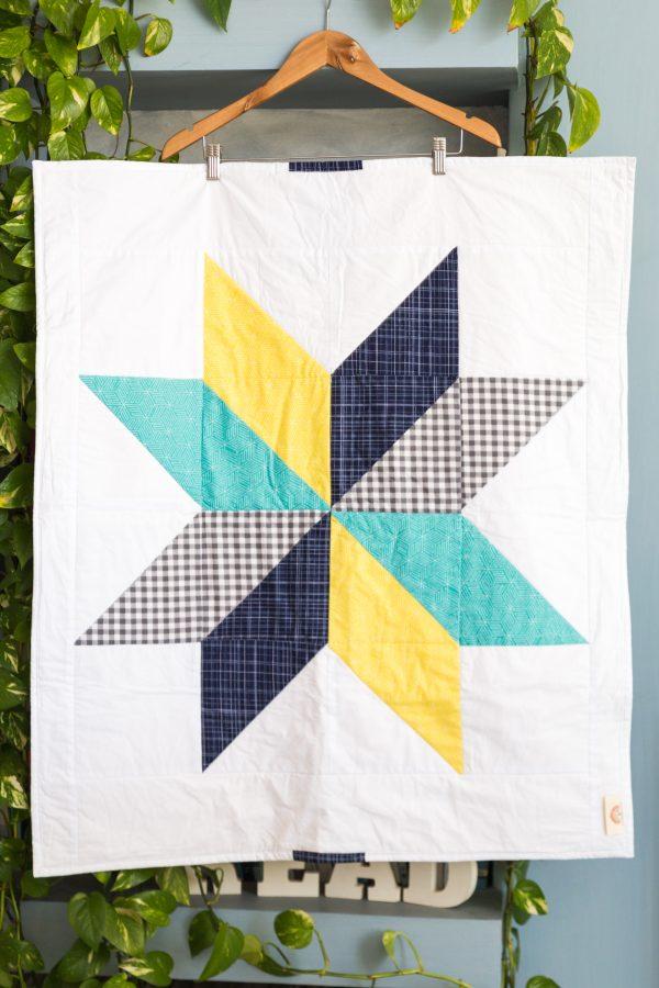 שמיכת טלאים בדוגמת כוכב בצבעי אפור, כחול כהה, טורקיז וצהוב.