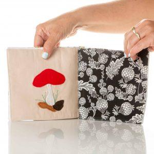 ידיים מחזיקות כפולה בספר. דף ימני עלים פרחים ופרות בשחור ולבן. דף שמאלי אקליקצית לבד של פטריה אדומה